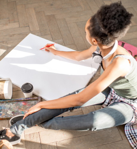 a femaile artist drawing on a large piece of paper